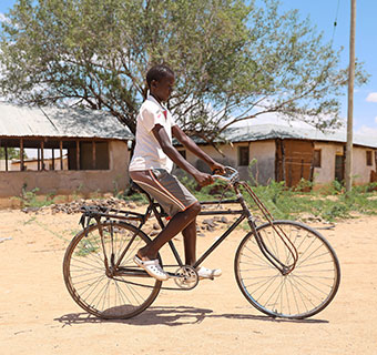 Mathew (13) fährt mit seinem Fahrrad durch sein Dorf in Turkana, Kenia. Hier lebt er mit seiner Familie. © Mark Njuguna / Save the Children