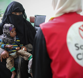 Badour* (15) hält ihre kleine Schwester Abir im Arm, während sie mit einer Save the Children Mitarbeiterin spricht. © Antonia Roupell / Save the Children